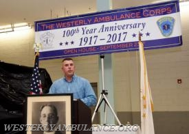 Philip B. Gingerella Sr. was the master of ceremonies at the Westerly Ambulance Corps' kickoff celebration of its centennial anniversary. Dr. Frank Payne, in the framed photo, founded the aumbulance service. | Christine Corrigan, The Westerly Sun