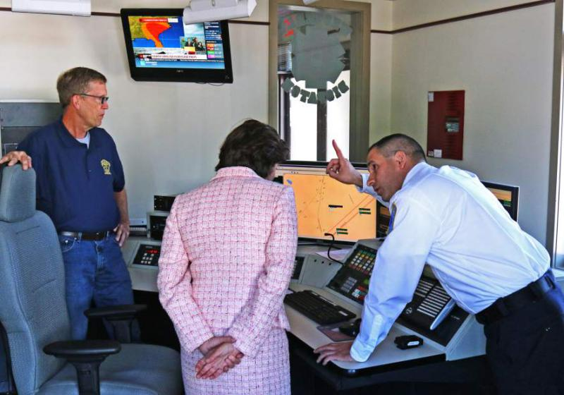 Westerly Ambulance Asst. Chief Michael Brancato explains working of the 911 center at the facility to Gov. Gina Raimondo on Friday, Sept. 8th, 2017. Looking on is Rob Palmer, a part-time dispatcher. The governor paid a brief visit to recognize the Westerly Ambulance Corps 100th anniversary.| Harold Hanka, The Westerly Sun