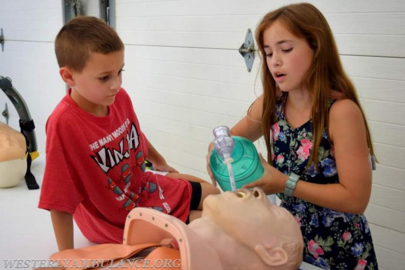 Levi and Hailey Mosher, 8 and 11, of Richmond, practice intubating a mannequin at the anniversary open house of the Westerly Ambulance Corps. Their father, Richard Mosher, is a captain with the corps.   Anna Sullivan, The Westerly Sun