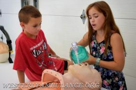 Levi and Hailey Mosher, 8 and 11, of Richmond, practice intubating a mannequin at the anniversary open house of the Westerly Ambulance Corps. Their father, Richard Mosher, is a captain with the corps. | Anna Sullivan, The Westerly Sun