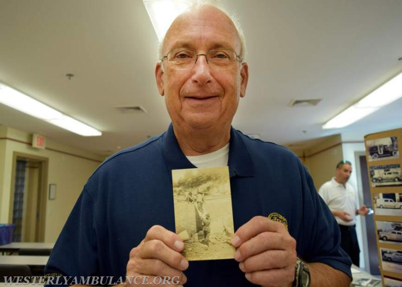 Tom Gibney, chaplain of the corps, holds up an old photo of ambulance workers practicing stretcher drills, probably from the turn of the last century.   Anna Sullivan, The Westerly Sun