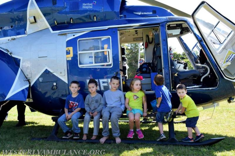 Children don't miss the chance to sit on the railing of the Lifestar Helicopter. Left to right are: Devin O'Reilly, Eli Davila, Derien Northup, Leah, Paul and Colton Latimer. All are from Westerly. The Westerly Ambulance Corps celebrates 100 years of service at the Chestnut Street location on Saturday, September 23, 2017. The event includes facility tours, food, drink, activities for children, demonstrations of CPR, and a visit from Hartford Hospital's Lifestar Helicopter.   Anna Sullivan, The Westerly Sun