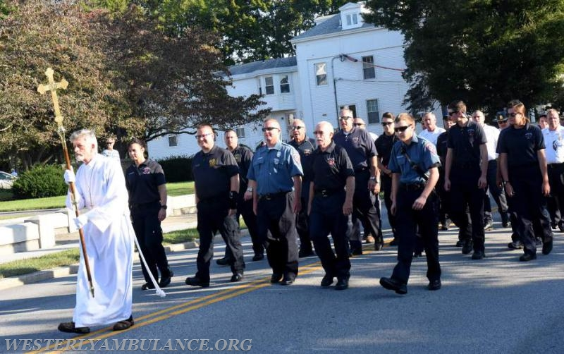 Seth Tulman, a Crucifier from Christ Church in Westerly walks in a procession with first responders and clergy on Elm Street to Christ Church for an interfaith blessing service.This event is organized by Rev. Cal Lord of Central Baptist Church and Rev. Sunil Chandy of Christ Church and other Faith leaders. First responder's vehicles and companies were blessed in a service in the parking lot of Central Baptist Church in Westerly on Sunday, September 24, 2017. | Christine Corrigan, The Westerly Sun