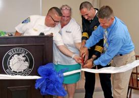 Ken Richards III, EMS administrator for the Westerly Ambulance Corps, CTE Medical Pathways Instructor Dawn Smith, Westerly Ambulance Asst. Chief Michael Brancato and WHS Assistant Principal Kevin Cronin cut the ribbon at the ceremonial ribbon cutting for the Westerly Public Schools CTE-Medical Pathways Program at the Westerly Ambulance Corps headquarters on Tuesday September 4, 2018. Harold Hanka, The Westerly Sun