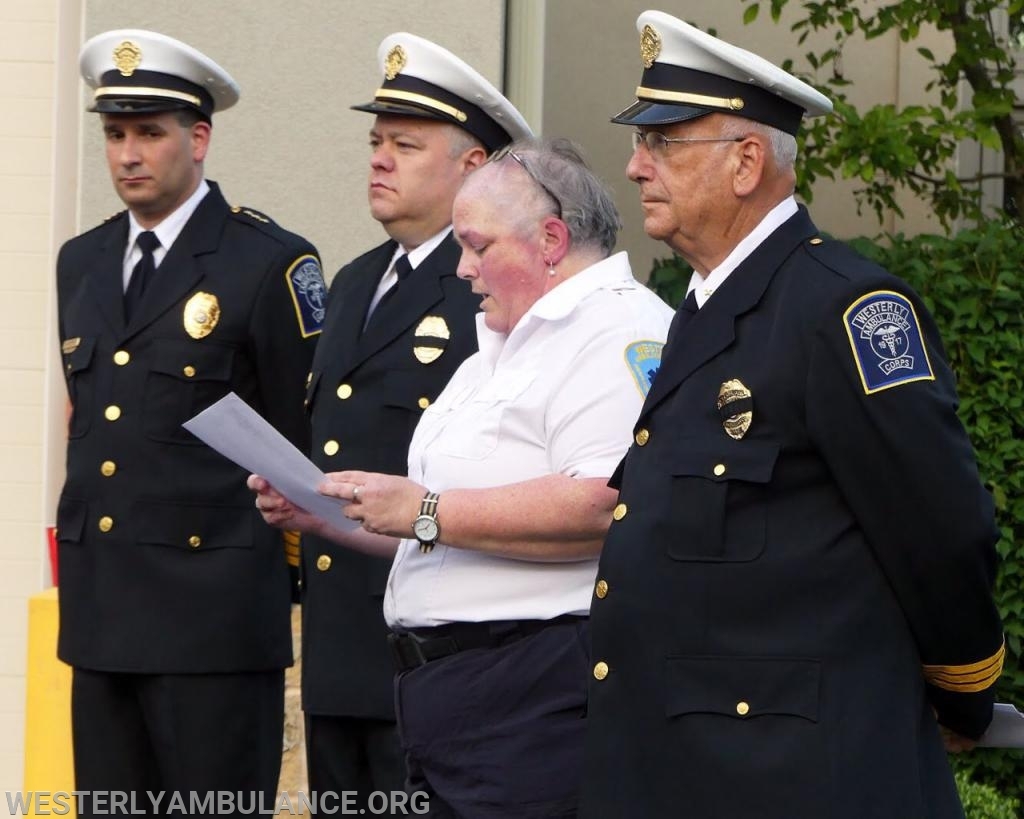 Dawn E. Smith, secretary of The Westerly Ambulance Corps reads a list of names of the deceased members Friday during a memorial service at the Corps headquarters in Westerly.  She was standing, from left, with Assistant Chief Michael T. Brancato, Acting Chief Ronald J. MacDonald III and Thomas M. Gibney, Jr. Memorial Committee Chairman. Photo by Harold Hanka, The Westerly Sun