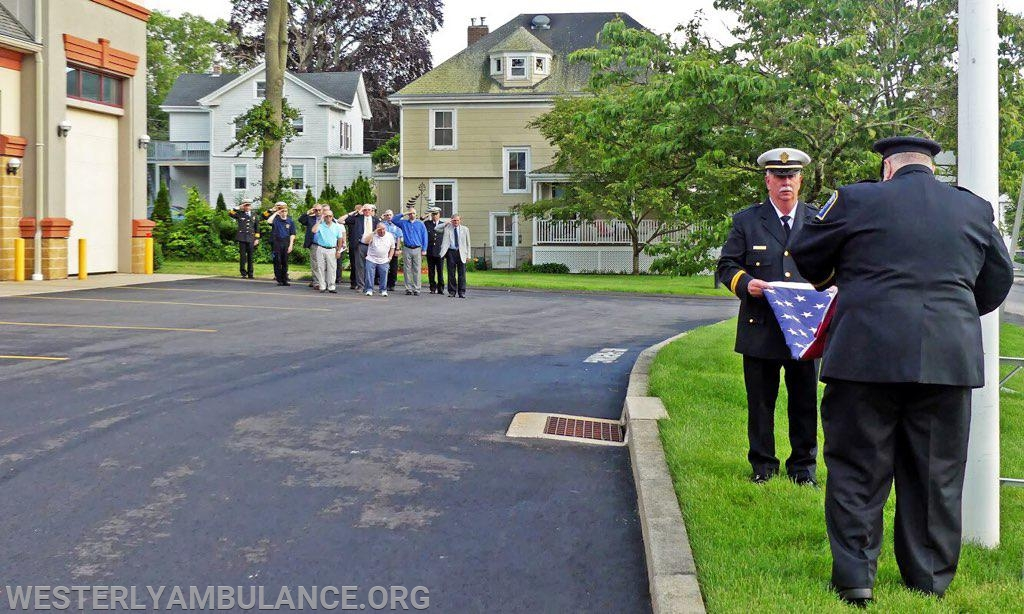 Members of the Westerly Ambulance Corps salute as the American flag is retired for the day by Charlie McGrath III and Mark Melanson during the memorial service held at the Westerly Ambulance Corps on Friday June 21, 2019.  Photo by Harold Hanka, The Westerly Sun